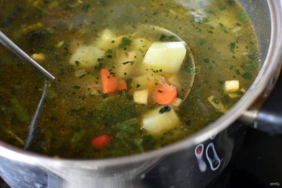 Опустите морковь, нарезанную тонкими кружочками, белую часть зеленого лука, нарезанную колечками. Дайте закипеть и выложите рубленый шпинат.