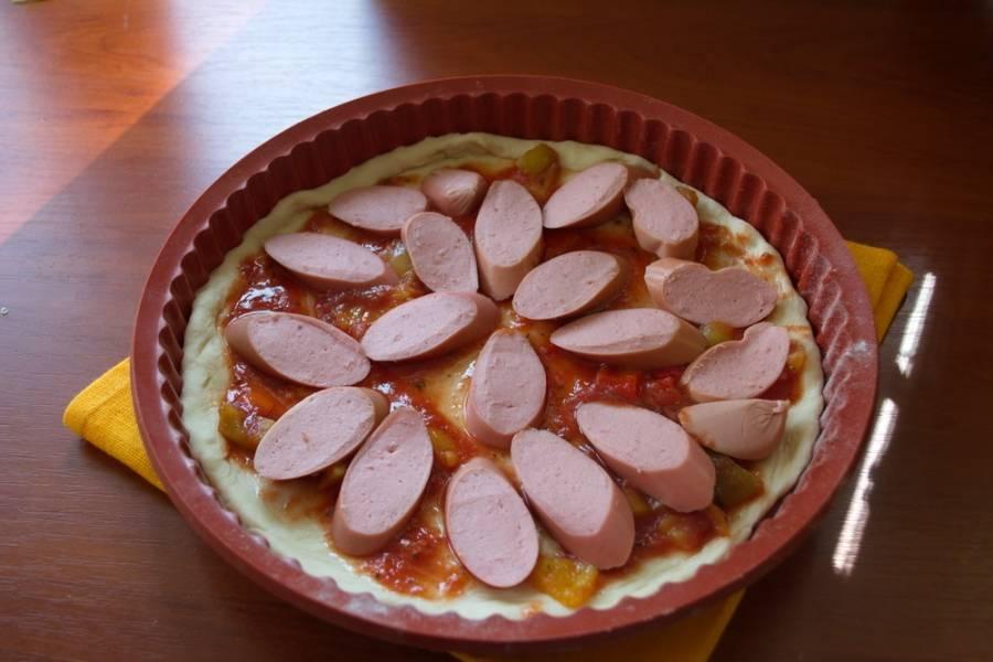 Корж пиццы смазать томатным соусом. Выложить нарезанный болгарский перец, сосиски. Перец можно взять и замороженный.