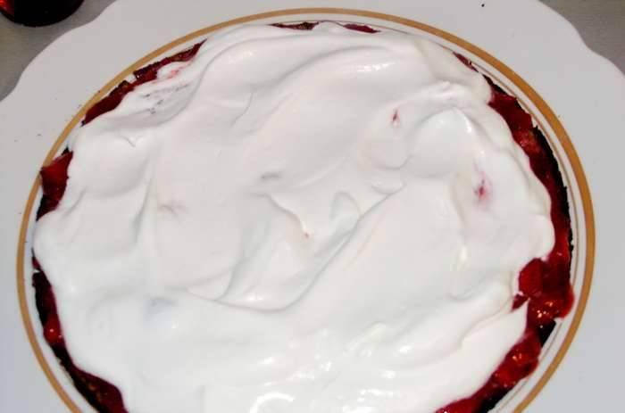 Охлаждённые сливки взбейте с сахарной пудрой на высоких оборотах. Два коржа пропитываем сиропом с ромом. Сверху выкладываем 1/2 часть клубничного пюре, затем 1/3 часть сливочного крема.