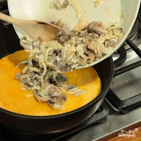 Обжаренные грибы выложите на омлет. Сковороду с блюдом поставьте в разогретую до 180 градусов духовку и запекайте 10 минут, до полной готовности.