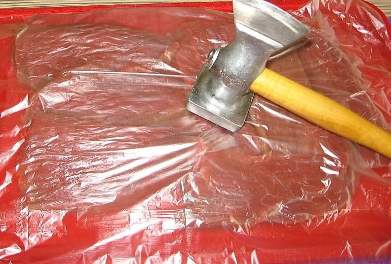 Для начала нам необходимо тщательно промыть говядину и высушить ее при помощи бумажных полотенец. Затем нарезаем мясо на кусочки шириной около 1 см поперек волокон, выкладываем их на разделочную доску, накрываем пищевой пленкой и отбиваем.