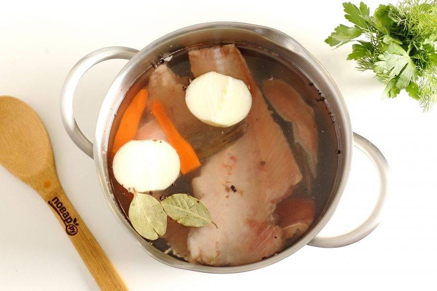 Рыбу промойте, сложите в кастрюлю, добавьте воду, лавровый лист, одну луковицу и морковь, разрезанные на части, перец горошком и соль по вкусу. Доведите до кипения и варите после закипания 20 минут.