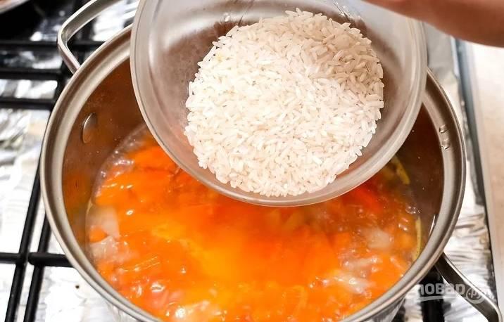 4. Доведите до кипения, посолите и добавьте специи по вкусу. Всыпьте промытый заранее рис. Варите на среднем огне до мягкости моркови (время зависит от размера кусочков и качества моркови). Готовность проверяем вилкой.