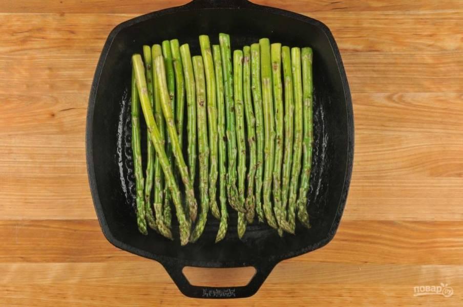 3. Спаржу сбрызните маслом и выложите на гриль. Запекайте её до готовности около 7 минут.
