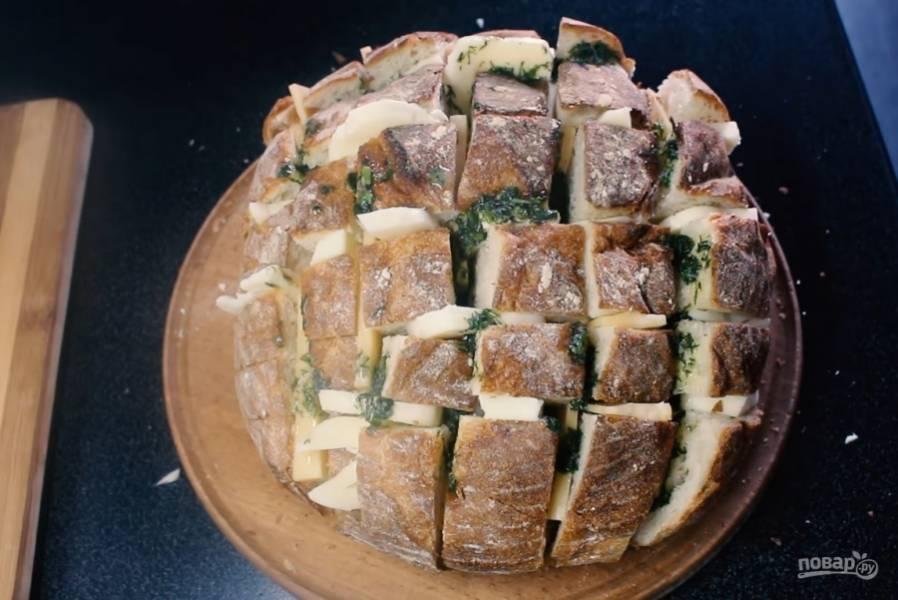 3.Сделайте надрезы вдоль и поперек хлеба, не дорезая до конца, и наполните эти разрезы начинкой. Старайтесь равномерно распределять сыр внутри разрезов. Залейте в разрезы сливочное масло с зеленью.