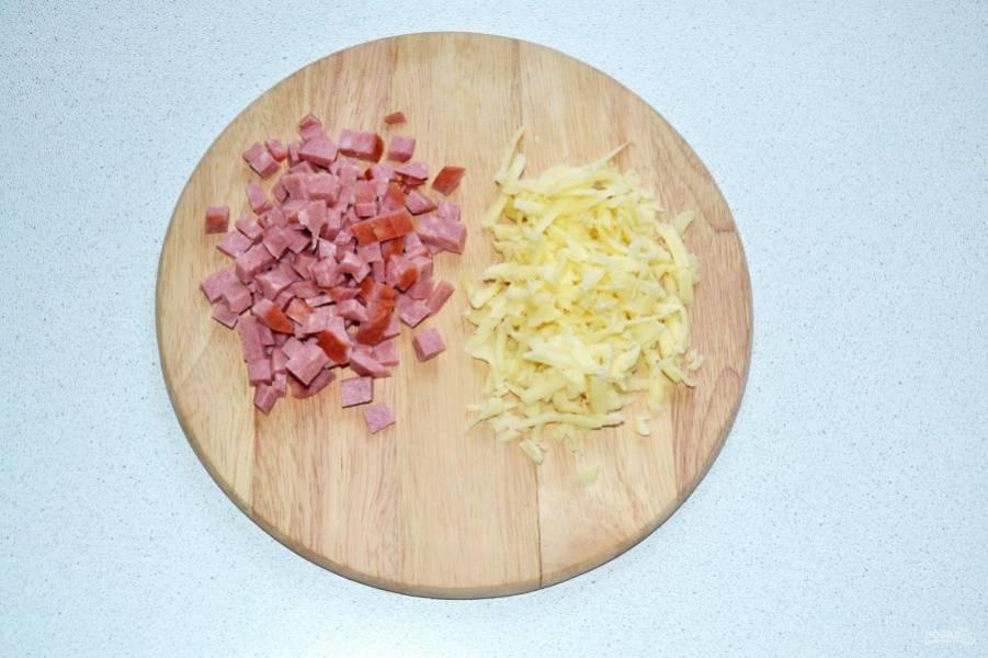Колбасу нарежьте небольшими кубиками, а сыр натрите на терке.