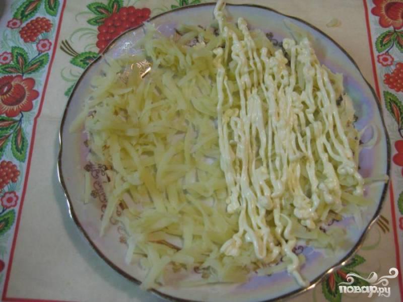 2.Промоем картофель, сварим, очистим его от кожуры, разрежем пополам и натрем на терке  по блюдцу, стараясь, чтобы слой был равномерным. Слой картофеля промажем майонезом.