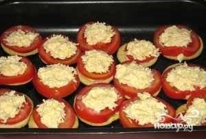 5. На противень стелим специальный пергамент, смазанный растительным маслом. Теперь выкладываем все ингредиенты на противень слоями. Первыми кладем баклажаны, посыпаем их тертым сыром. Немного перчим. На сыр выкладываем кружочки помидоров, снова перчим и солим.