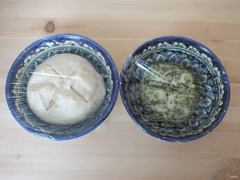 Возьмите две чашки, положите в них подготовленное тесто, сделайте крест на крест разрезы, затяните пленкой, накройте полотенцем и уберите в теплое место на 1,5 часа.