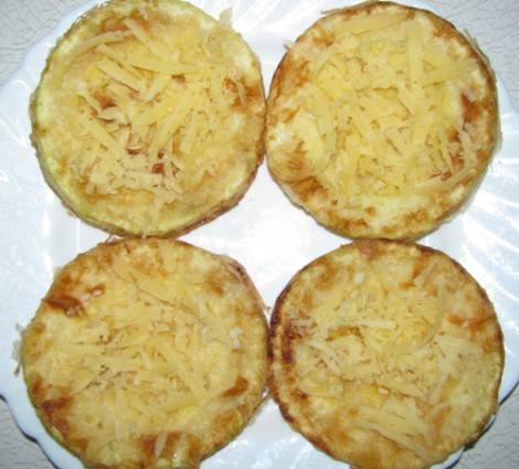 Присыпаем кабачки измельченным чесноком и присыпаем тертым сыром.