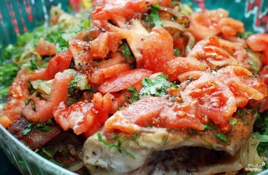 Сверху выкладываем помидоры. Поливаем блюдо маринадом и отправляем в предварительно разогретую до 240 градусов духовку где-то на 40 минут. Каждые 5-7 минут следует обязательно поливать рыбу соком, который собирается в форме.
