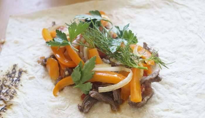 Лаваш разрезаем таким образом, чтобы можно было завернуть в него подготовленные ингредиенты. Кладем на часть лаваша мясо с помидорами, сверху выкладываем маринованный лук и перец. Присыпаем измельченной зеленью.