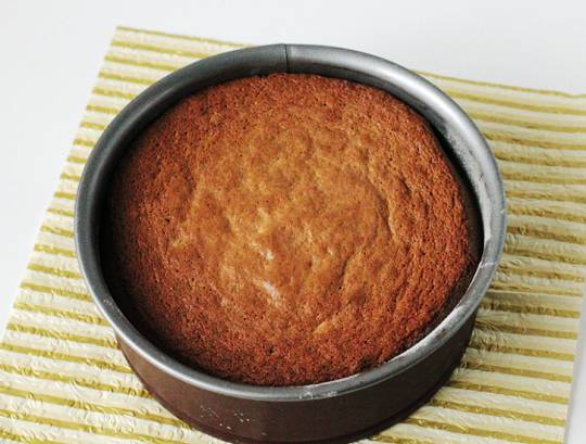 Шоколад растопите в горячих сливках, добавьте коньяк и перемешайте. Нижний корж смажьте вареньем, накройте вторым и со всех сторон обмажьте шоколадной глазурью. Украсьте сладкими фисташками.