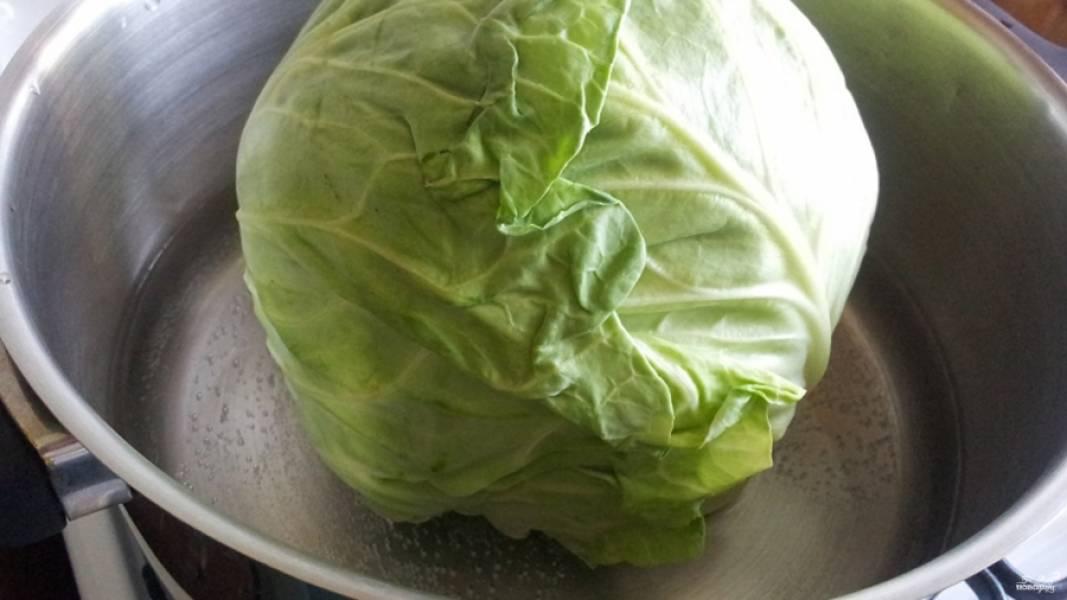 Для начала необходимо подготовить капусту. В большой кастрюле поставьте кипятиться воду. Тем временем хорошо вымойте капусту. При помощи длинного острого ножв вырежьте кочерыжку. Когда вода закипит, окуните туда капусту на несколько минут, а затем разберите её на листья.
