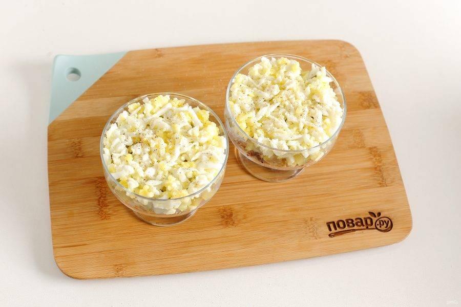 Сверху натрите на крупной терке вареные яйца. Слега посолите, поперчите и смажьте слой майонезом.