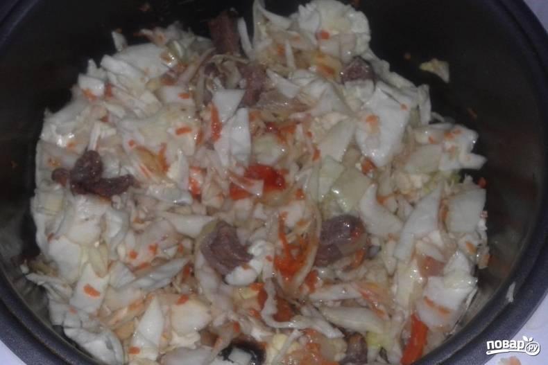 """Тем временем нашинкуйте капусту и выложите ее в чашу мультиварки, добавьте остальное растительное масло, включите режим """"Тушение"""" и готовьте блюдо около 40 минут, добавив соль и перец, томатную пасту и перемешав все."""