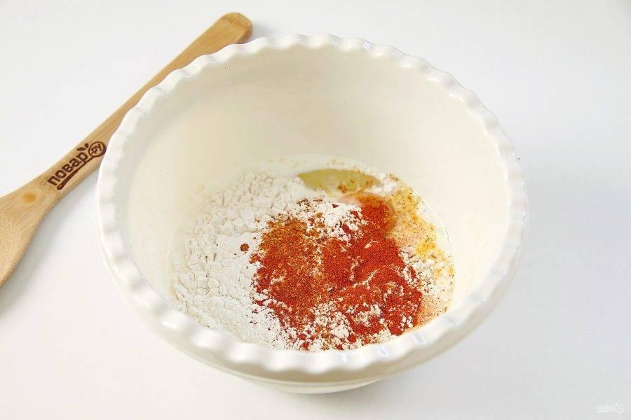 Сделайте соус: разбейте яйцо, влейте молоко и добавьте полстакана муки. Взбивайте до состояния жидкой сметаны. Добавьте сюда же столовую ложку соли, столовую ложку паприки и столовую ложку специй. У меня специи для курицы, вы можете добавить любые другие на свой вкус.