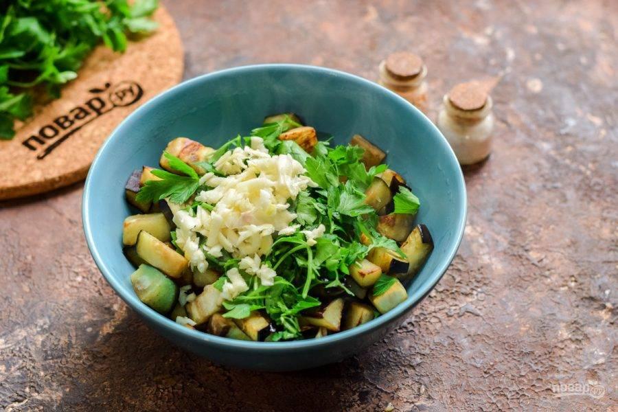 Переложите готовые баклажаны в миску, добавьте чеснок, зелень.