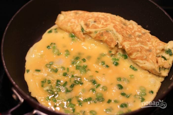 4.Аккуратно отодвиньте рулет из омлета на край сковороду и налейте еще часть яичной смеси.