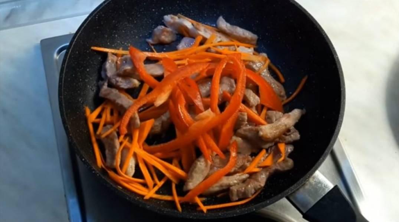 2. Добавьте морковь, перемешайте. Добавьте болгарский перец, опять перемешайте. Добавьте лук и сливы, все перемешайте и оставьте на сковороде на 3-4 минуты.