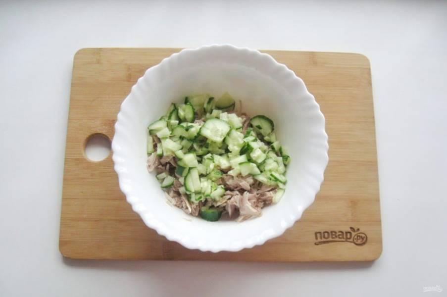 Свежий огурец помойте и нарежьте кубиками. Добавьте в салат.