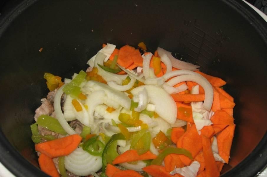 2. Дальше добавим измельченные лук, баклажаны, перец, картошку, морковь и чеснок. Обжарим еще 15 минут.