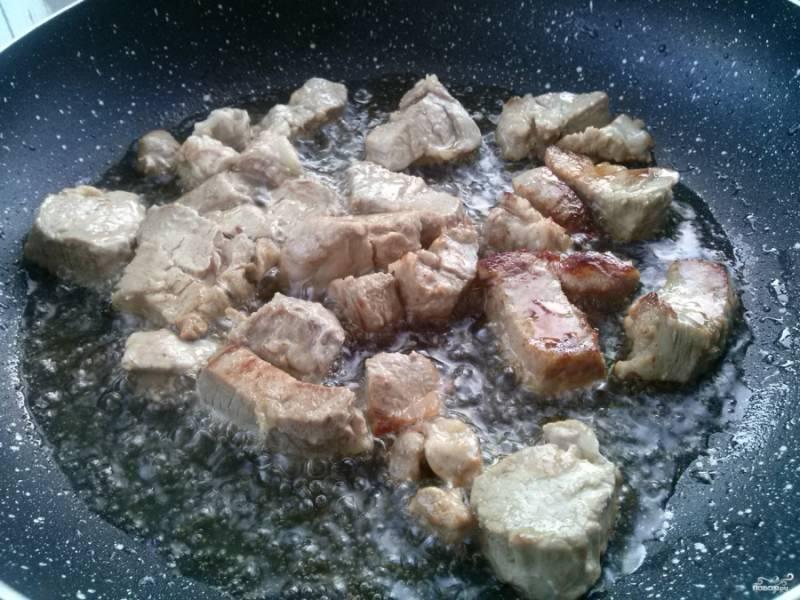 Разогрейте растительное масло на сковороде, выложите туда кусочки мяса, обжарьте его до румяной корочки.