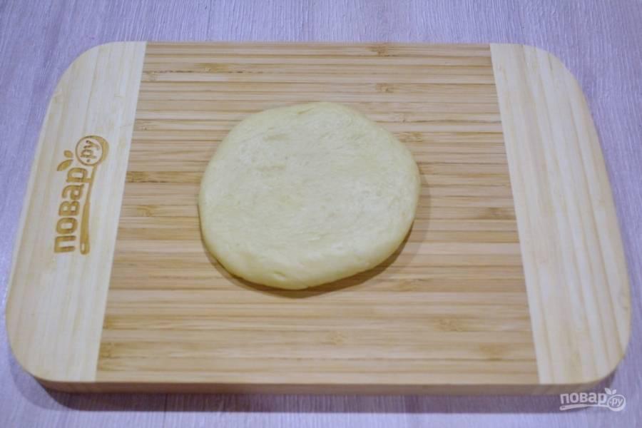 Для приготовления петушка берите дрожжевое тесто. Его можно купить в магазине или приготовить дома. Подойдет совершенно любой рецепт теста для пирожков. Из небольшой части теста скатайте шарик и слегка разомните его руками в блин, чтоб получился вот такой круг. Для ориентира нужен кусочек теста размером с не очень крупный апельсин. Используйте муку для посыпки и припудривания рук.