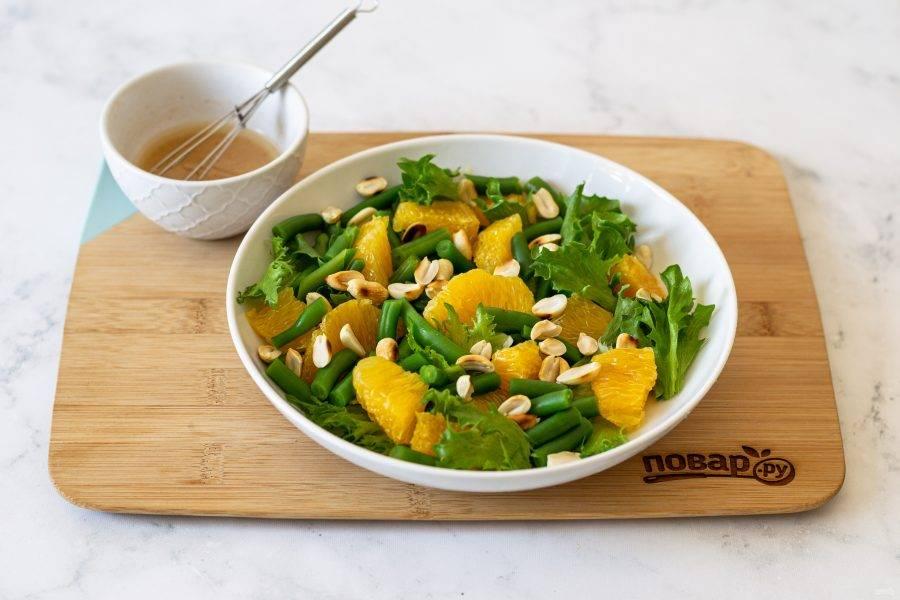 В миску выложите листья салата фризе, апельсин, фасоль и поджаренный арахис. Заправьте салат.