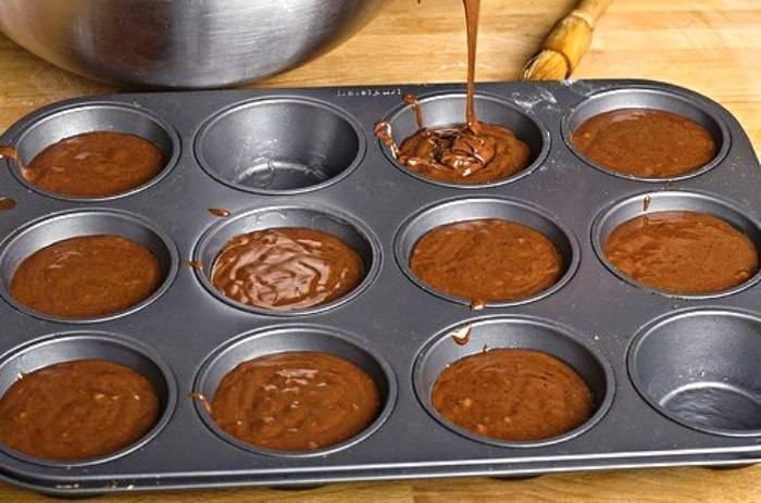 Смажьте формы для кексов растительным маслом, наполните их на треть тестом (кексы поднимутся). Выпекайте в течение получаса в духовке, разогретой до 180 градусов. Готовые кексы остудите и при желании посыпьте сахарной пудрой.