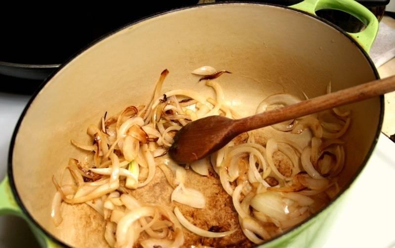 1. На сковороду или на дно сотейника налить немного растительного масла. Очистить и нарезать тонкими полукольцами луковицу. Отправить в разогретое масло и обжарить слегка. При желании рецепт приготовления свинины с баклажанами и помидорами можно дополнить чесноком.