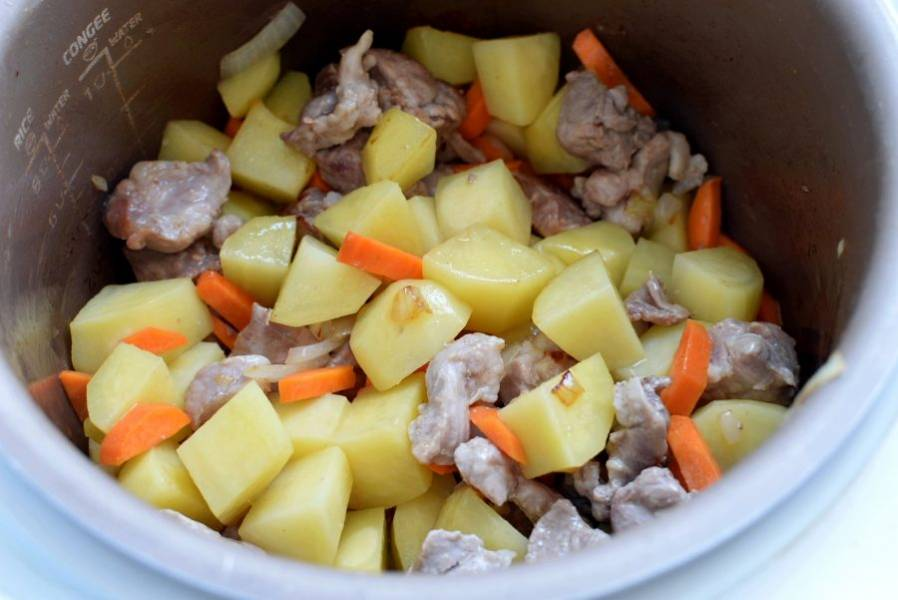 Добавьте морковь брусочками и крупно порезанный картофель. Жарьте 3 минуты.