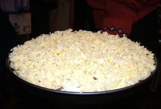 И посыпаем тертым на крупной терке сыром. Теперь накрываем форму крышкой или фольгой и ставим в разогретую до 200-220 градусов духовку на пол часа.