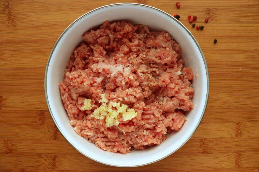 В фарш добавьте измельченный чеснок, соль и перец по вкусу. Чеснок для этого блюда раздавливают плоской стороной ножа, а затем мелко нарезают.