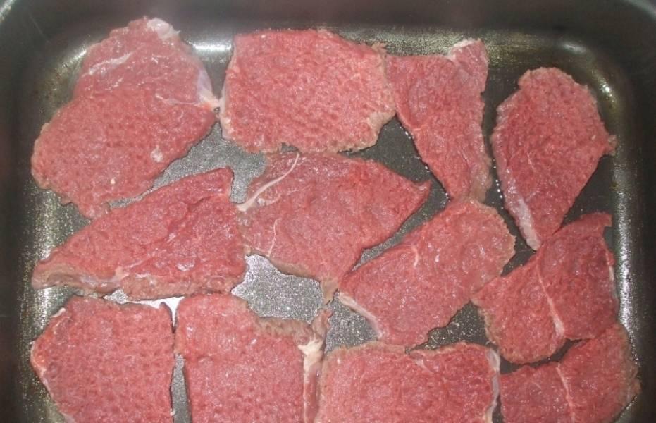 Выкладываем мясо на противень, смазанный маслом.