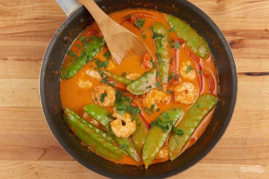 5. Затем добавьте соль, перец, креветки и кинзу. Тушите блюдо 5 минут, иногда помешивая.