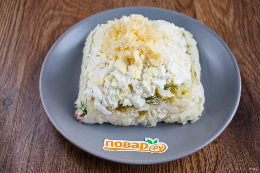 Переверните салат на блюдо, снимите пленку. Лопатками или плоской стороной ножа сформируйте из салата пирамиду. Верхний треугольник сформируйте из тертого сыра.