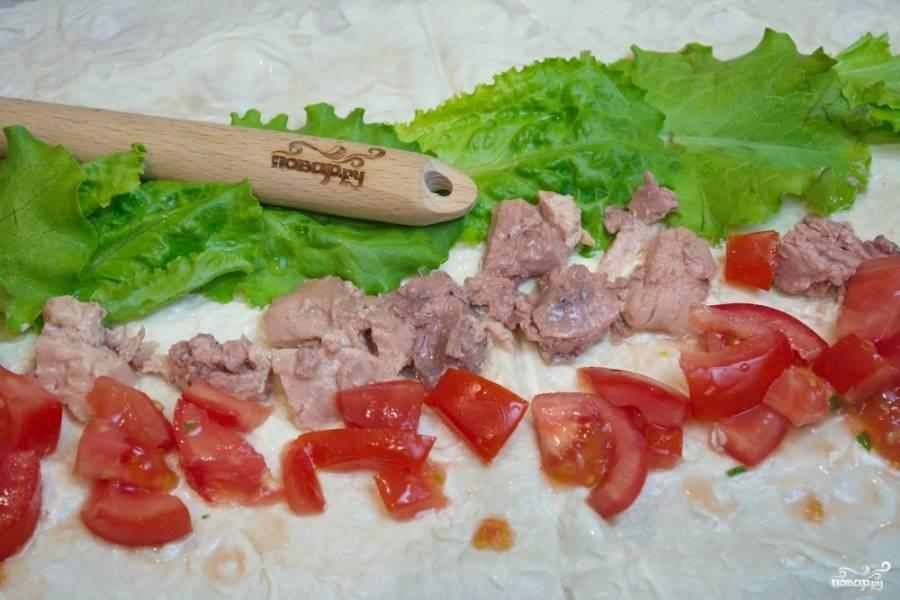 Теперь выложим начинку для рулета. Измельчите промытые листья салата. Порвите их руками. Выложите их на лаваш рядком. Свежий помидор нужно нарезать небольшими кусочками и выложить следующим рядом. Извлеките из банки печень трески. Лишнее масло лучше слить. Печень нарезаем на небольшие кусочки или разминаем вилкой.