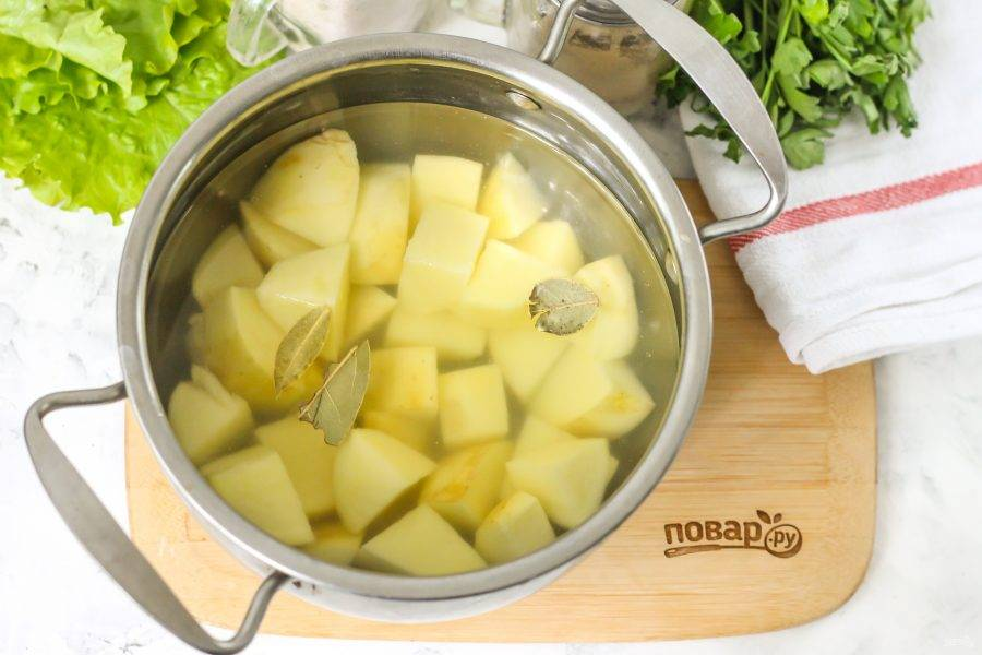 Картофель нарежьте средними кубиками и выложите нарезку в кастрюлю, влейте горячую воду, добавьте лавровые листья и поместите емкость на плиту. Доведите до кипения и отварите картофель примерно 15 минут.