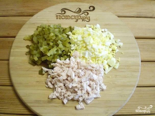 Порежьте кубиками огурцы, яйца и мясо. Оставьте часть огурцов и яиц для украшения.