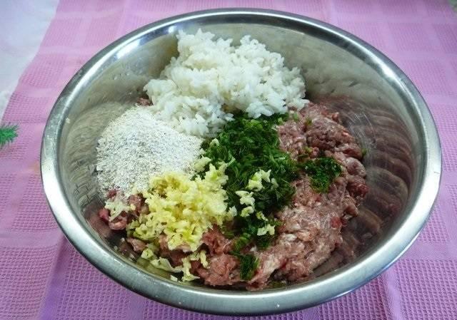 1. Для приготовления фарша необходимо пропустить через мясорубку мясо (можно сочетать свинину и говядину или курицу, например). Измельчить чеснок и свежую зелень. Рис отварить до полуготовности, а хлопья залить кипятком. Посолить и поперчить все по вкусу, добавить любимые специи и сушеные травы (в данном случае используются кориандр, базилик, орегано и паприка). Вбить яйцо и как следует все перемешать.