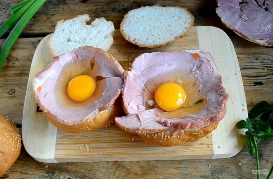 В полученное углубление вложите тонкий ломоть ветчины и аккуратно влейте яйцо. Следите, чтобы оно поместилось в углублении и не вытекло.
