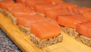 1. Сразу же отварим яйца и оставим их остужаться. Хлеб подсушим на сухой сковороде или в духовке, тоже остужаем. Режем хлеб на 16 квадратиков, поверх каждого размещаем по кусочку семги.