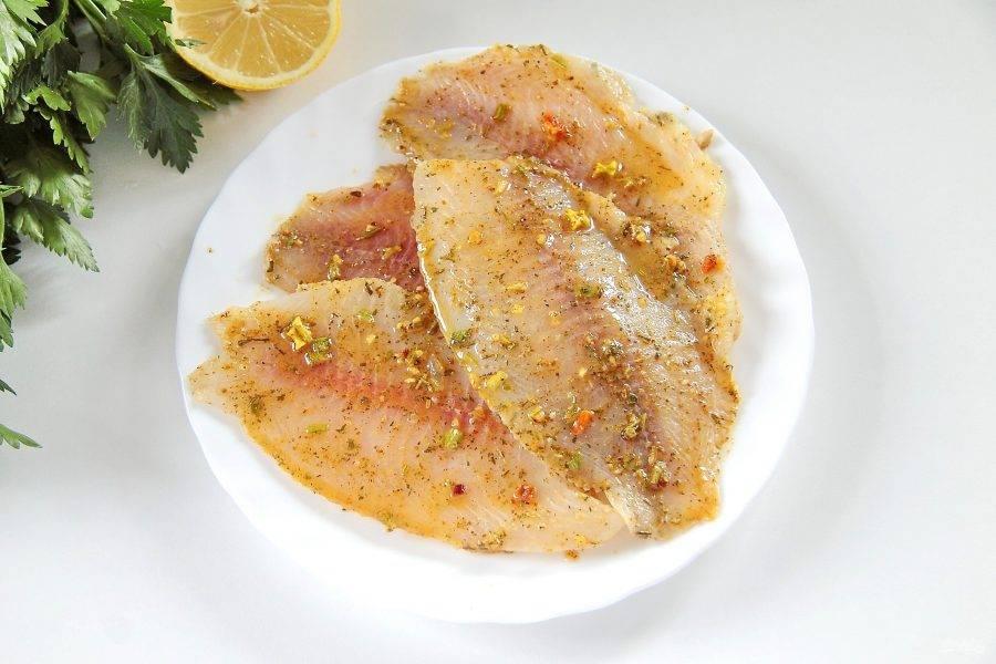 2. Натрите готовое филе тилапии солью и специями, полейте соком лимона. Оставьте рыбу мариноваться на 20-30 минут. Я оставляю филе целым, но по желанию можно разрезать каждое еще на две части. Специи можно использовать любые любимые, у меня уже готовая смесь специально для рыбы в состав которой входят: кориандр, сушеные овощи, куркума, паприка, тимьян и перец.