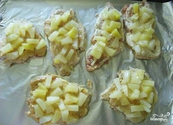 4. Обжаренные отбивные выложить на противень, предварительно застеленный фольгой и немного смазанный растительным маслом. Слегка смазать майонезом. Сверху выложить кусочки ананасов.