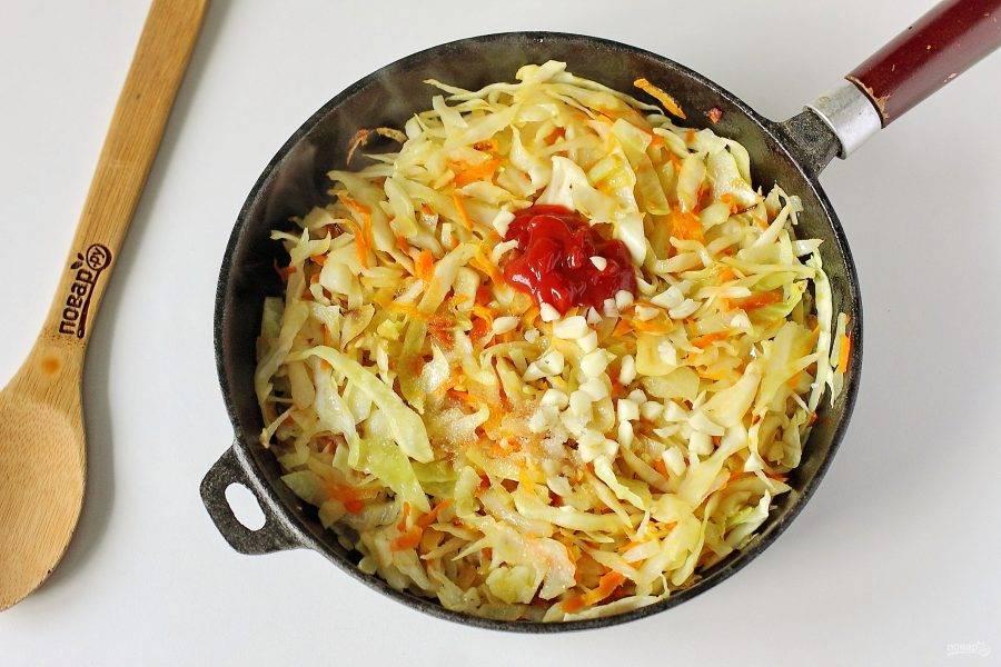 Как только капуста пустит сок и станет мягкой, добавьте томатную пасту, измельченный чеснок, сахар и соль по вкусу.