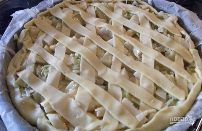 Взбейте яйца с солью, перцем и щепоткой мускатного ореха, залейте начинку. Из остатков песочного теста нарежьте полоски, украсьте пирог «решеткой».