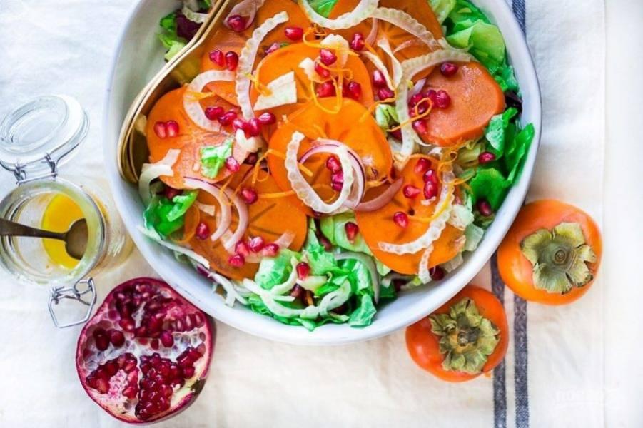 Затем нарвите в салатницу промытый латук, выложите хурму, фенхель и лук. Посыпьте ингредиенты гранатом и полейте заправкой. Салат готов! Приятного аппетита!