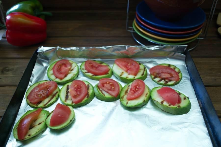 На противень уложите лист фольги. Сверху на фольгу выложите кабачки. На каждый кабачок - по кусочку помидора.
