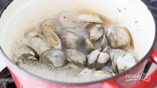 1. Моллюски тщательно промойте. Потом выложите их в кастрюлю с вином. Варите, пока все раковины не раскроются. На это уйдёт около 30 минут.
